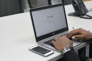 hands on laptop, screen showing google